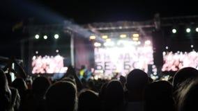 La folla della gente illuminata da luce variopinta durante il concerto, fan salta al festival rock, molti fuoco colorato in scena stock footage