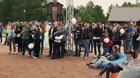 La folla della gente resta con i palloni sulla sabbia pubblici Festival di estate Bambini stock footage