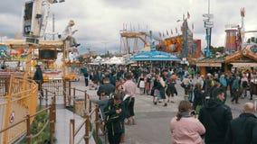La folla della gente sta camminando lungo la via centrale del festival di Oktoberfest La Baviera, Germania archivi video