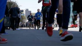 La folla delle gambe dei corridori degli atleti e della gente funziona lungo la strada nella città stock footage