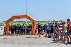 La folla e gli atleti si riuniscono alla linea di inizio di triathlon dell'incrocio di Kijkduin fotografie stock libere da diritti