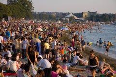 La folla multiculturale si riunisce al tramonto sulla baia inglese, Vancouver Immagine Stock