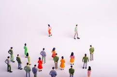 La folla sta esaminando l'uomo e la donna che sono separati su un fondo bianco Un uomo e una donna vanno l'uno dall'altro PS fotografia stock libera da diritti