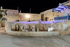 La fontaine avec des chiffres du zodiaque se connecte la place de Kdumim la nuit dans la vieille ville Yafo, Israël Photos stock
