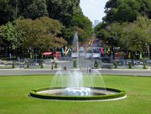La fontaine, la pelouse et les touristes d'eau en dehors de du palais Saigon de l'indépendance Images stock