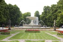 La fontana corrente con le sculture nel parco Fotografia Stock