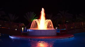 La fontana nella piscina all'albergo di lusso nell'illuminazione di notte archivi video