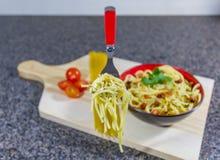 La forcella di galleggiamento della tagliatella in aglio ed olio, è servito in una ciotola con bacon ed i pomodori immagini stock libere da diritti