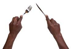 La forcella ed il coltello che sono tenuti vicino equipaggia le mani Fotografia Stock