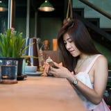 La forma de vida de las mujeres utilizó un teléfono móvil en café Fotografía de archivo libre de regalías