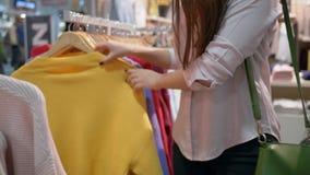 La forma de vida del comprador, clientes que las manos de la muchacha están eligiendo la nueva ropa de moda en boutique se cierra almacen de metraje de vídeo