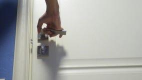 La forma de vida masculina de la mano del hombre abre la puerta fuera del cuarto Viaje del concepto del alojamiento de hotel El h almacen de video