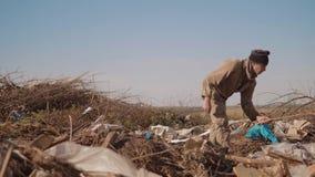 La forma de vida masculina sucia que el hombre hambriento sin hogar en una descarga bebe buscar la comida de la ropa en el paquet almacen de metraje de vídeo