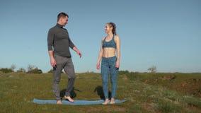 La forma de vida sana, par se relaja antes de entrenar en aire fresco mientras que se coloca en la estera de los deportes que lle metrajes