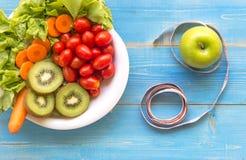 La forma de vida sana para las mujeres adieta con la cinta métrica, manzanas frescas, verdes vegetales azules en de madera Imagen de archivo