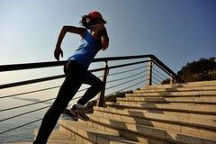 La forma de vida sana se divierte a la mujer que corre para arriba en la salida del sol de piedra de las escaleras Foto de archivo