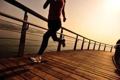 La forma de vida se divierte a la mujer que corre en la playa de madera de la salida del sol del paseo marítimo Imagen de archivo libre de regalías