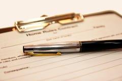 La forma del contrato con una pluma en un fondo blanco Imágenes de archivo libres de regalías