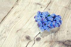 La forma del corazón con nomeolvides florece en la madera rústica Fotografía de archivo libre de regalías