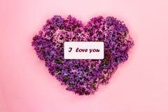 La forma del corazón hizo de las flores púrpuras de la lila con la inscripción te amo en fondo rosado en colores pastel S?mbolo d fotografía de archivo