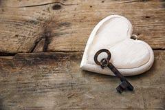 La forma del cuore fatta di bianco ha dipinto il legno e una vecchia chiave su rustico Fotografia Stock