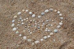 La forma del cuore ha fatto delle conchiglie sulla sabbia fotografia stock libera da diritti