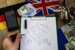 La forma di carta una struttura su una tavola di legno con i contenitori di regalo ha imballato il Mo Immagine Stock