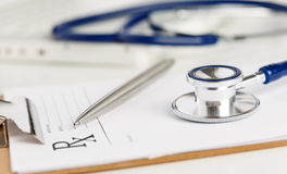 La forma di prescrizione ha tagliato per riempire la menzogne sulla tavola con lo stetoscopio Fotografia Stock