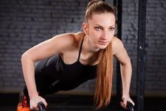 La forma fisica che di Crossfit la bella donna spinge aumenta Kettlebells, facente l'esercizio all'allenamento della palestra Fotografia Stock