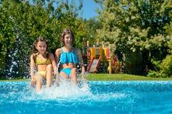La forma fisica dell'estate, bambini nella piscina si diverte, spruzzata sorridente delle ragazze in acqua fotografia stock libera da diritti