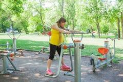 La forma fisica della donna incinta all'aperto parcheggia Immagini Stock Libere da Diritti