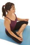 La forma fisica della donna medita sull'angolo Fotografia Stock