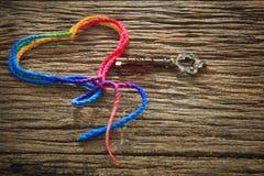 La forma y la llave coloridas del corazón del hilado en el uso texturizado madera del fondo para el amor firman adentro día de San Imagen de archivo