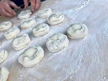 La formación de pedazos de pasta para los pasteles de las empanadas en una superficie de madera floured imagen de archivo