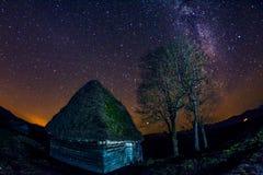 La formación estelar de la vía láctea vista en una noche clara cerca de un pueblo abandonado viejo con las construcciones rústica imágenes de archivo libres de regalías