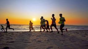 La formation d'équipe de football extérieure sous le coucher du soleil de plage Photo stock