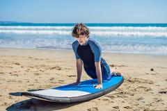 La formation de surfer de jeune homme avant vont à la ligne sur une plage de sable L Photos libres de droits