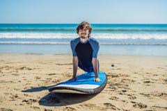 La formation de surfer de jeune homme avant vont à la ligne sur une plage de sable L Photographie stock