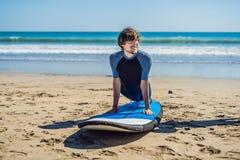 La formation de surfer de jeune homme avant vont à la ligne sur une plage de sable L Image stock