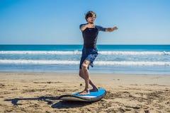 La formation de surfer de jeune homme avant vont à la ligne sur une plage de sable L Photo libre de droits