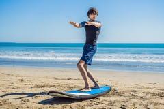 La formation de surfer de jeune homme avant vont à la ligne sur une plage de sable L Image libre de droits
