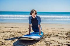 La formation de surfer de jeune homme avant vont à la ligne sur une plage de sable L Photos stock