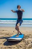 La formation de surfer de jeune homme avant vont à la ligne sur une plage de sable L Images stock