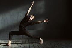 La formation habile de danseur dans l'obscurité a allumé la pièce Photographie stock libre de droits