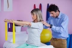 La formation supérieure de femme avec la bande d'exercice a aidé par le physiothérapeute Photo stock