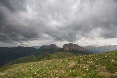 La formazione ed i movimenti di nuvole fino ai pendii ripidi delle montagne di Caucaso centrale alza Immagine Stock Libera da Diritti