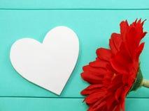 La forme blanche de coeur et le gerbera artificiel rouge fleurissent Images libres de droits