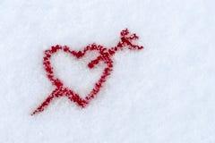 La forme d'un coeur rouge percé par une flèche dans la neige dans le wint Photo stock