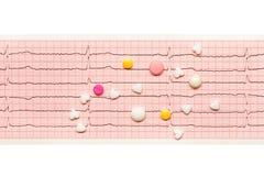 La forme de coeur, blanc, jaune, les comprimés roses sur ECG de papier résulte Image libre de droits
