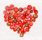 La forme de coeur a coupé en tranches des fraises sur le fond en bois blanc Photographie stock